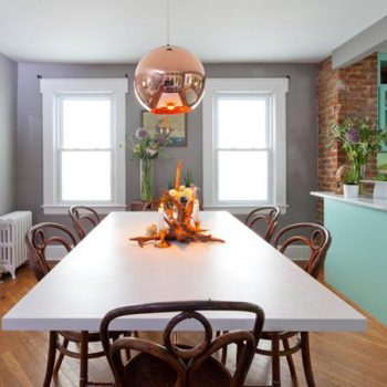 A modern copper pendant light is the showstopper in this updated dining space, as seen on HGTV's Cousins Undercover.